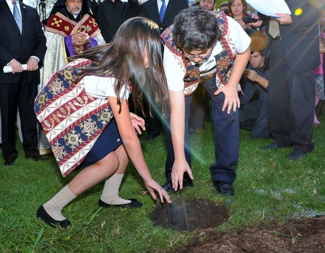 Sevana Wasslian and Zareh Apkarian place a glass cylinder of soil from Armenia at the base of the Armenian Genocide Centennial Monument, during the monument's groundbreaking ceremony at Fresno State.  Photo by Alain Ekmalian